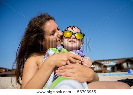 Happy young mother and son on a tropical beach with the laughing little boy. The boy points Sun Protection