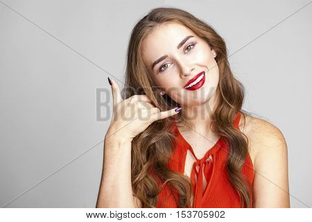 Call me a pretty young brunette woman, isolated on gray background
