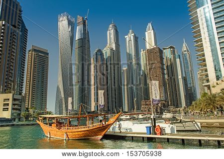 DUBAI, UAE - OCTOBER 09, 2016. View of various skyscrapers in Dubai Marina with stunning turquoise waters and a traditional dhow boat as foreground