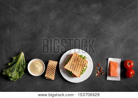 Club sandwich prepared with fish on the black chalkboard. Top view