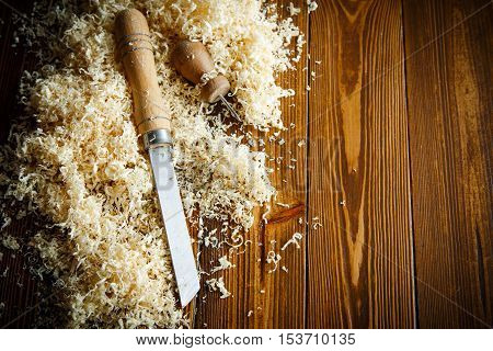 Woodworking tools. Chisel with sawdust on a wooden table
