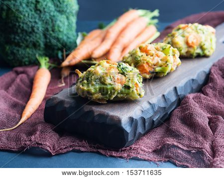 Baked vegetable patties with carrots, broccoli and cheese on dark wooden serving board