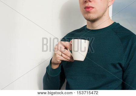 Young man holding a cup and drinks coffee, tea at work, home.