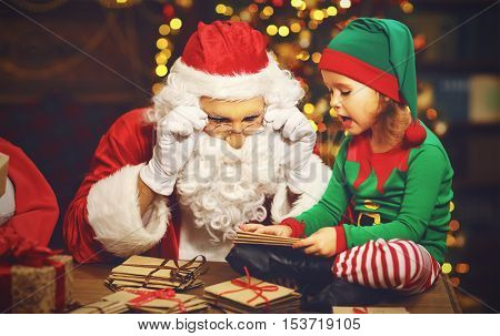 Santa Claus and a elf child in a Christmas working reading letters and prepare gifts