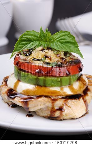 Chicken breast with slices of mozzarella avocado tomato and basil