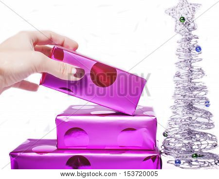 woman manicured hand puting christmas gift to rest pile of purple gifts close up isolated silver little tree, post card