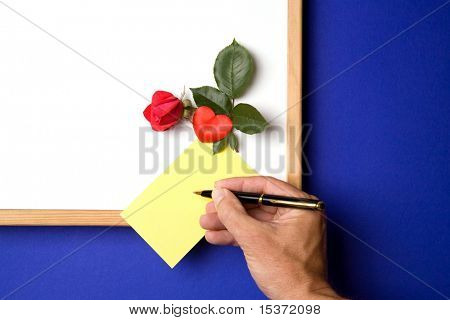 white-board with empty yellow post-it note a magnet in the form of a heart and a red rose