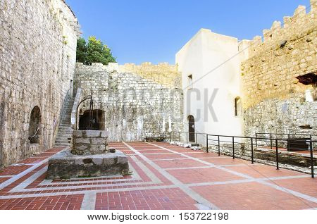 KRK TOWN, CROATIA - 22 August, 2015: The interior of the Frankopan Castle at Kamplin square in Krk Croatia - Frankopanski Kastel part of the medieval city walls. View of the courtroom the well stern square tower and archer loop holes.