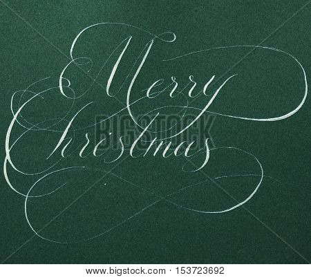 The inscription Merry Christmas calligraphy in gold silver ink on green paper