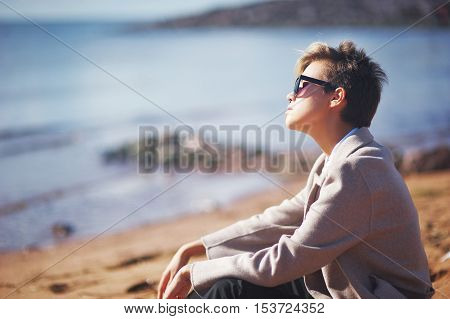 Dreamy stylish girl in fashion clothing and dark glasses sitting on the rocks under the rays of the autumn sun.
