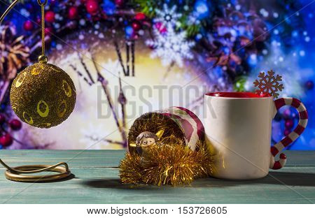 Christmas theme with toy ball angel and mug on green wooden surface against nice clock background.