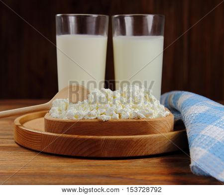 dairy product,fresh cottage cheese in wooden ware with a spoon and milk in glasses