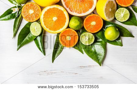 Citrus background. Assorted fresh citrus fruits with leaves. Lemon, orange lime, grapefruit mandarin. Harvest concept. Top view. wooden white background. Copy space
