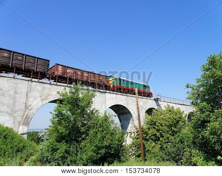 Shunting diesel locomotive rides with gondolas on a viaduct.