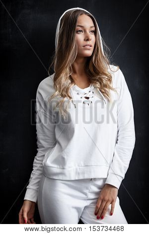 Young trendy woman in white sportsuit posing near black wall