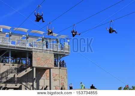 NIAGARA FALLS, ONTARIO - OCT 12,2016. Here we see four people launch from the new zipline attraction known as Wild Play's Mist Rider. On a hot October day they will descend the escarpment to a platform below near the Horseshoe Falls