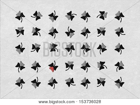 A grid of black and grey clovers with only one having a red leaf
