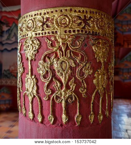 typical Thai gold sculpture on red pole.