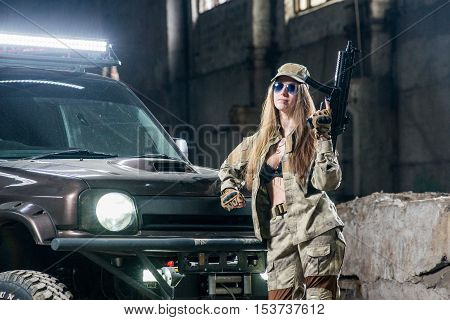 Attractive girl near the SUV , standing in uniform with automatic rifle in his hands