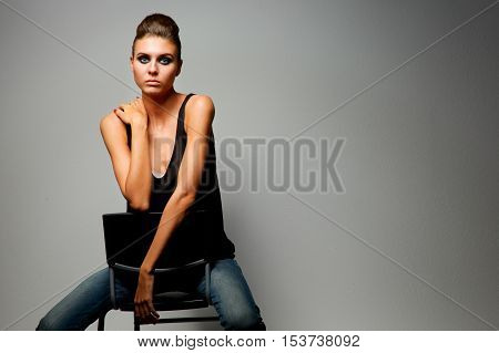Beautiful woman sitting a chair, isolated on gray background.