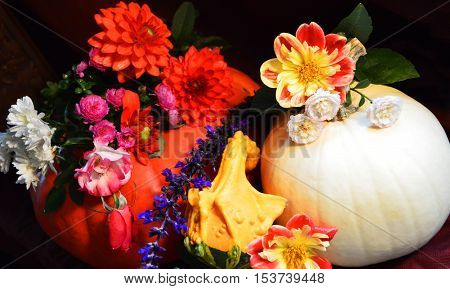Beautiful Floral Pumpkin Centerpiece with autumn harvest colorful red and white pumpkins, gourds and autumn flower bouquet including roses and chrysanthemums in an abundance of color celebrating the fall season