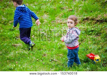 two kids playing on a green lawn toys.