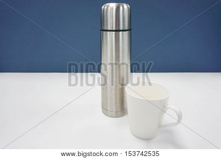 thermos bottle with white mug on office desk