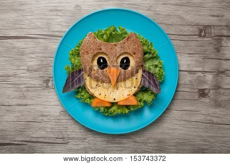 Owl made of bread and cheese on plate and board