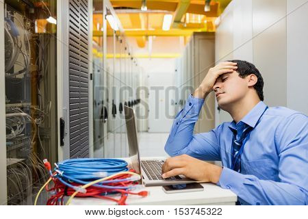 Stressed technician working laptop in server room