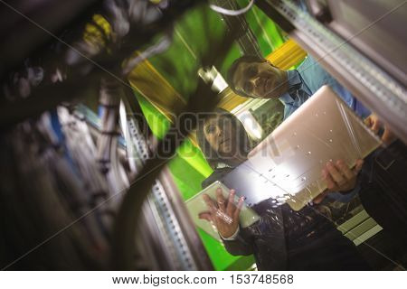 Technicians using digital tablet and laptop while analyzing server