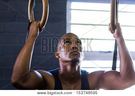 Close-up of man using gymnastic rings while exercising in gym