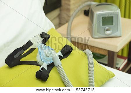 CPAP headgear mask with air tube connecting to CPAP machine in bedroom