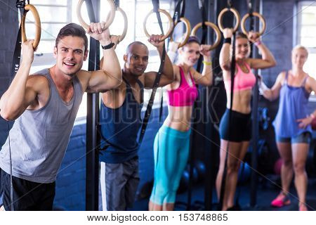 Portrait of smiling people with gymnastic rings in gym