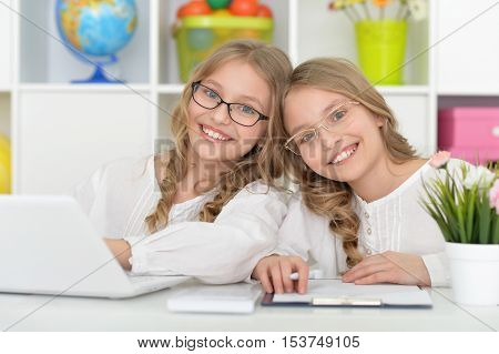 Two beautiful little girls at class with laptop