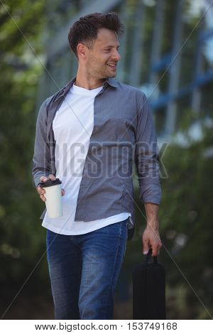Handsome business executive holding disposable cup and bag outside office