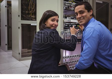 Portrait of technicians analyzing server in server room