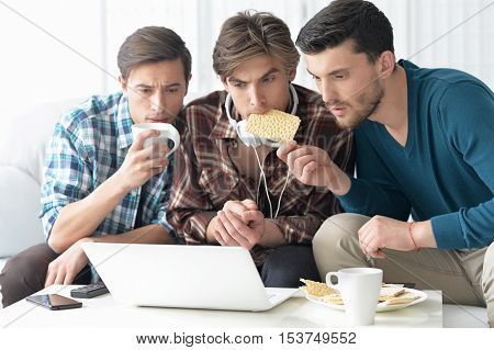 handsome men watching video on laptop together