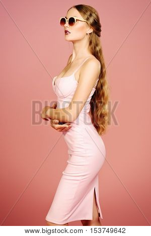 Glamorous young woman wearing elegant fitting dress and sunglasses posing over pink background. Beauty, fashion concept. Evening dresses collection.