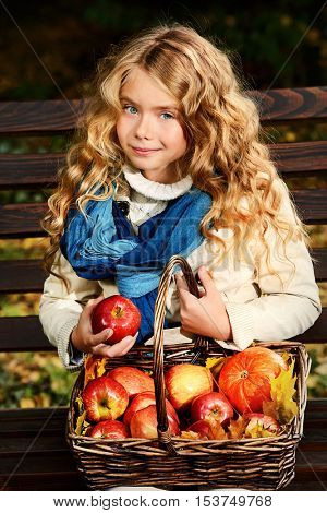 Lovely little girl sitting on a bench with a basket of red apples in a beautiful autumn park. Children's fashion.