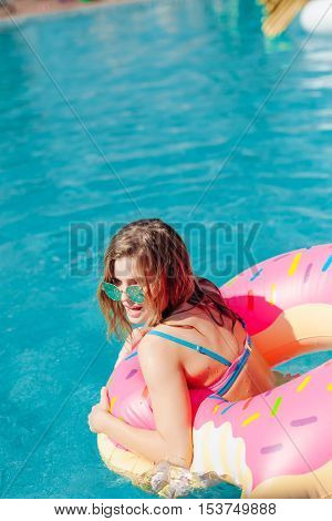 Young hipster millennial girl in sprinkled donut float at pool 20s