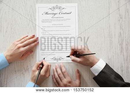 Couple signing marriage contract, closeup