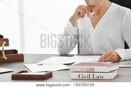 Female lawyer working with documents in office, close up view