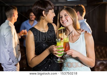 Smiling female friends holding glass of cocktail in bar