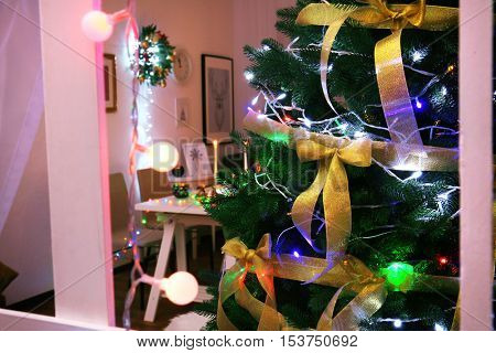 Beautiful decorated Christmas tree at night, view from window