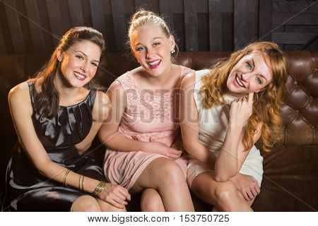 Portrait of smiling female friends sitting together in sofa at bar