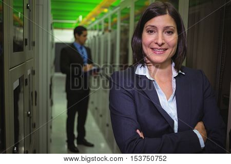 Portrait of female technician standing with arms crossed in server room