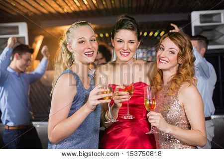 Portrait of smiling female friends holding a glass of champagne in bar