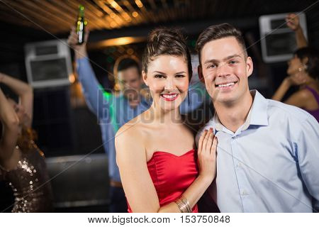 Portrait of cute smiling couple standing together in bar