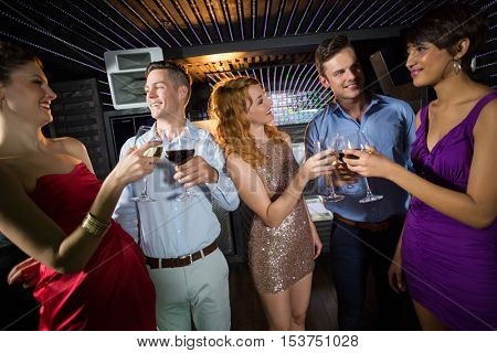 Group of smiling friends toasting glasses of champagne and wine in bar