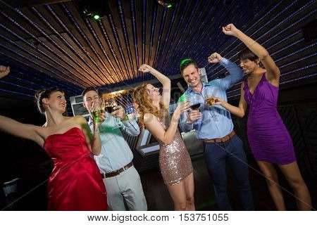 Smiling friends holding glasses of champagne and wine while dancing at bar